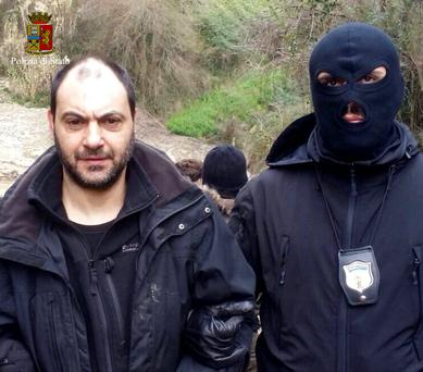 A police officer escorts fugitive Giuseppe Ferraro in this handout picture released by the Italian Police on January 29, 2016. REUTERS/Italian Police/Handout via Reuters