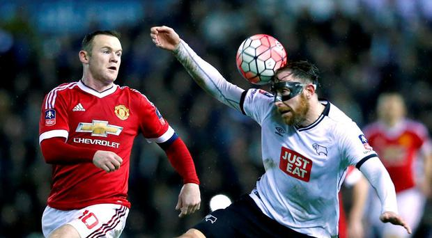 Richard Keogh heads the ball clear under pressure from Wayne Rooney. Photo: Eddie Keogh / Reuters