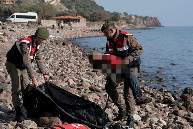 A Turkish paramilitary police officer holds the lifeless body of a boy near the Aegean town of Ayvacik, Canakkale, Turkey, Saturday, Jan. 30, 2016. (AP Photo/Halit Onur Sandal)
