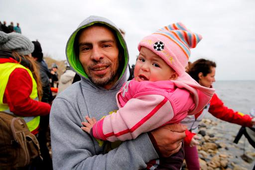 A migrant carries his baby after arriving on a rubber dinghy packed with refugees on a beach on the Greek island of Lesbos Credit: Darrin Zammit Lupi (REUTERS)