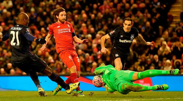 Liverpool's Welsh midfielder Joe Allen (2nd L) has his shot blocked by West Ham United's Irish goalkeeper Darren Randolph during the English FA Cup fourth round football match between Liverpool and West Ham United at Anfield