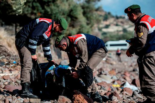HORRIFYING SCENES: Turkish police officers put the body of a child into a body bag on a beach in Canakkale's Bademli district after at least 39 migrants drowned when their boat, below, capsized in the Aegean Sea while trying to cross from Turkey to Greece. Photos: Getty Images