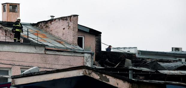 Firefighters and investigators work at the site of a fire in a Moscow factory on January 31, 2016. At least 12 people, including three children, perished in a fire in a Moscow factory that caused the roof to collapse, Russian authorities said on January 31