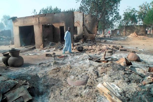 A man walks past burnt out houses following an attack by Boko Haram in Dalori village 5 kilometers (3 miles) from Maiduguri, Nigeria, Sunday Jan. 31, 2016. A survivor hidden in a tree says he watched Boko Haram extremists firebomb huts and listened to the screams of children among people burned to death in the latest attack by Nigeria s homegrown Islamic extremists