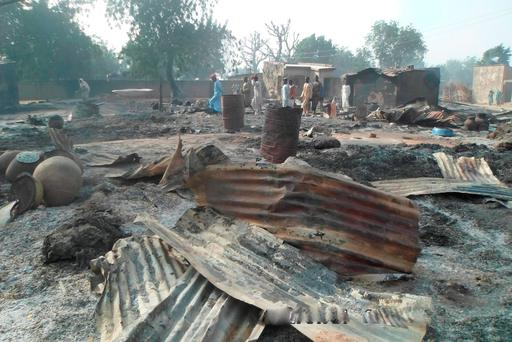People walk past burnt out houses following an attack by Boko haram in Dalori village 5 kilometers (3 miles) from Maiduguri, Nigeria , Sunday Jan. 31, 2016. A survivor hidden in a tree says he watched Boko Haram extremists firebomb huts and listened to the screams of children among people burned to death in the latest attack by Nigeria s homegrown Islamic extremists