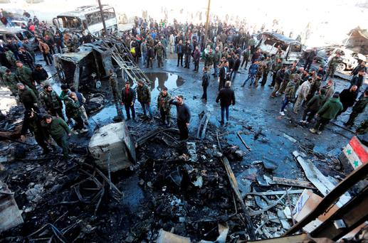 Syrian pro-government forces and residents gather at the site of suicide bombings in the area of a revered Shiite shrine in the town of Sayyida Zeinab, on the outskirts of the capital Damascus, on January 31, 2016