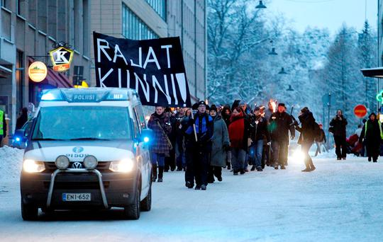 Anti-immigration marchers are led by a police van on the streets in Tampere, Finland