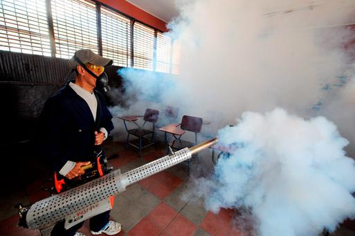 A health official fumigating a school in Honduras. Getty Images
