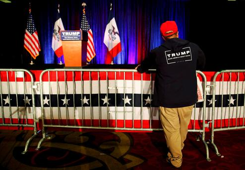 Austin Bayliss of Altoona, Iowa, watches as the stage for U.S. Republican presidential candidate Donald Trump's caucus night rally is taken down in West Des Moines, Iowa, February 1, 2016. REUTERS/Scott Morgan TPX IMAGES OF THE DAY