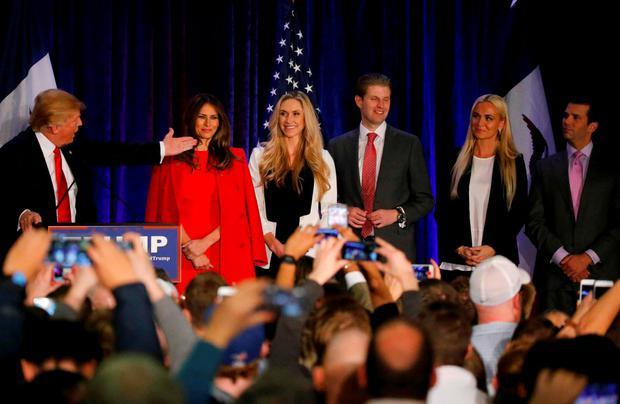 Republican Presidential Candidate Donald Trump speaks with his family onstage at a caucus night rally in Des Moines, Iowa February 1, 2016. REUTERS/Carlos Barria
