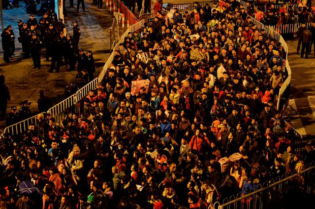 Passengers wait to enter a railway station in Guangzhou Credit: China Daily