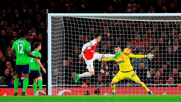 Arsenal's Mesut Ozil has an attempt on goal saved by Southampton goalkeeper Fraser Forster during the Barclays Premier League match at The Emirates