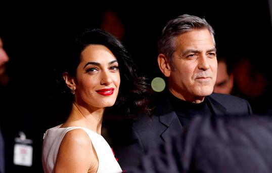 Cast member George Clooney and his wife Amal pose at the premiere of