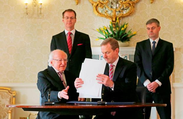 General to the President Art O'Leary (back left) and Secretary General at the Department of the Taoiseach, Martin Fraser (back right) watch as Taoiseach Enda Kenny (right) and President Michael D Higgins sign an order dissolving the Irish Parliament and starting the 2016 general election campaign at Aras an Uachtarain. Photo: Niall Carson/PA Wire