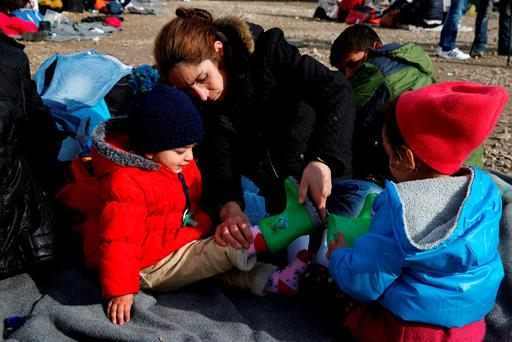 A migrant fits boots on to her child as refugees and migrants wait to continue their journey towards western Europe from the Macedonia-Serbia border at a transit camp in the village of Presevo. Photo: Darrin Zammit Lupi/Reuters