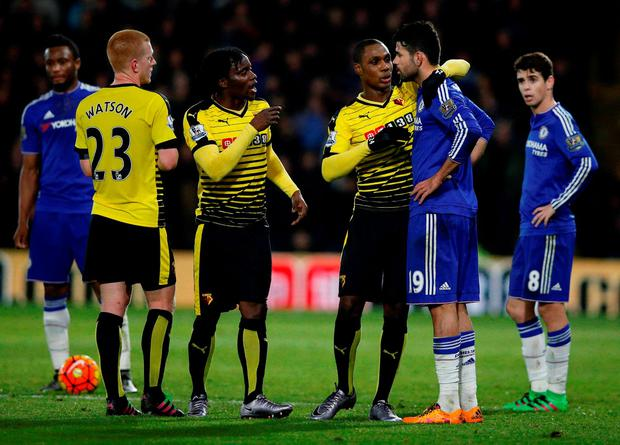 Watford's Nigerian striker Odion Ighalo (3R) stands between Chelsea's Brazilian-born Spanish striker Diego Costa (2R) and Watford's Ecuadorian defender Juan Carlos Paredes (3L) in the aftermath of a sequence of incidents that saw both Costa and Paredes booked during the English Premier League football match between Watford and Chelsea at Vicarage Road