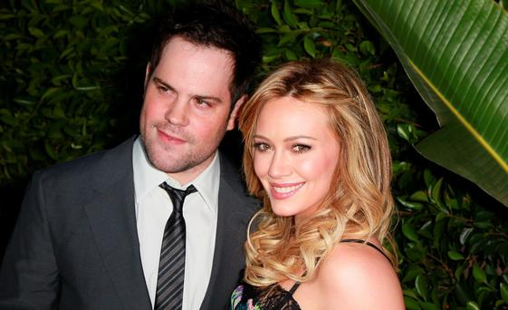 Professional hockey player Mike Comrie (L) and wife actress Hilary Duff attend An Evening of