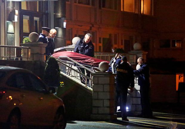 A man's body is removed from the scene of the shooting at the Regency Hotel last night