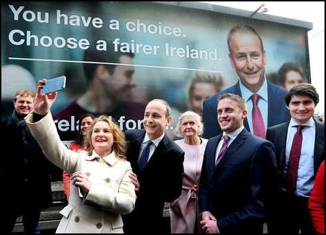 Fianna Fáil's Mary Fitzpatrick takes a 'selfie' with party leader Micheál Martin, Senator Mary White and Councillor Cormac Devlin at the launch of their General Election campaign at their election headquarters on Mount Street, Dublin. Photo: Steve Humphreys