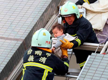 Rescue workers remove a baby from the site where a 17-storey apartment building collapsed after an earthquake hit Tainan. Reuters/Stringer