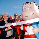"""2003 file photo: The real Linus, artist Linus Maurer, cuts a ribbon after unveiling a statue of Linus of """"Peanuts"""" comic strip fame during a ceremony at his hometown of Sleepy Eye, Minn. (John Cross/The Free Press via AP)"""