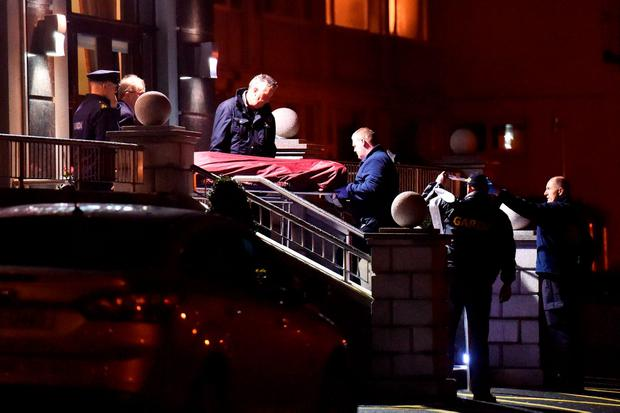 Gardai remove a body from the scene of a shooting at the Regency Hotel in Dublin