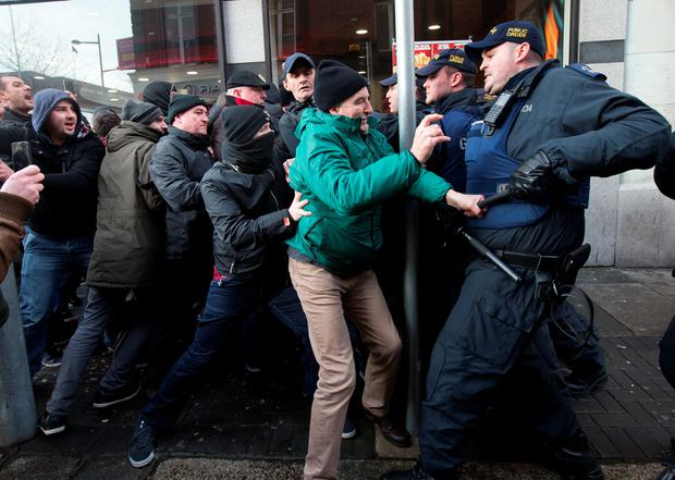 A garda grapples with protestors on Cathedral Street during the anti Pegida rally today. Photo: Tony Gavin