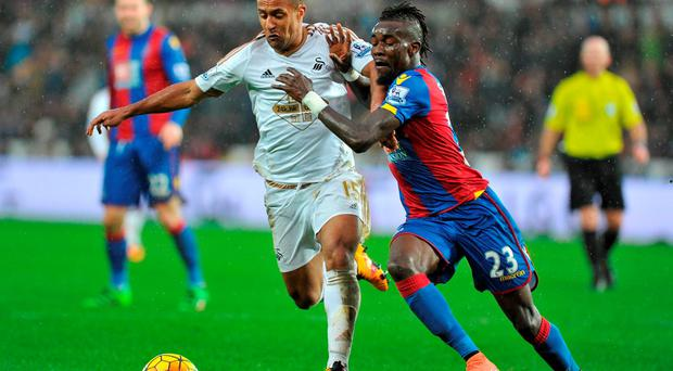 Swansea City's Wayne Routledge (left) and Crystal Palace's Pape Souare battle for the ball. Photo: PA