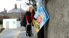 Mary Mitchell O'Connor of Fine Gael hanging election posters in Dun Laoghaire. Photo: Justin Farrelly