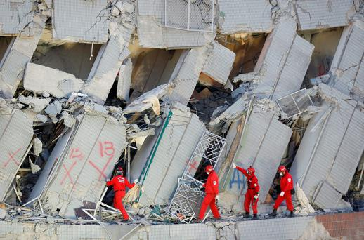 Emergency rescuers continue to search for missing in a collapsed building from an earthquake in Tainan, Taiwan. (AP Photo/Wally Santana)