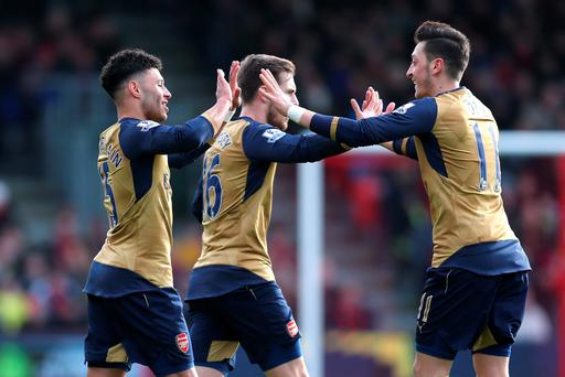 Alex Oxlade Chamberlain celebrates with team mates after scoring the second goal for Arsenal