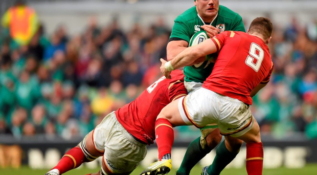 CJ Stander is tackled by Taulupe Faletau, left, and Gareth Davies
