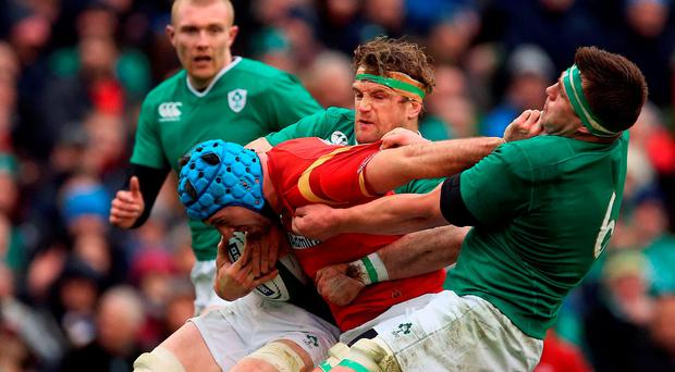Wales' Justin Tipuric tackled by Ireland's CJ Stander (right) and Jamie Heaslip