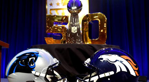 The Vince Lombardi Trophy sits on the table along with the helmets of the Carolina Panthers and the Denver Broncos