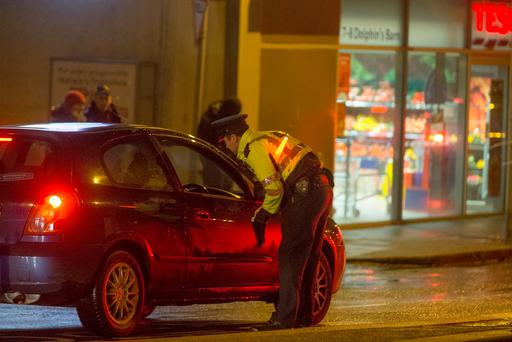Gardaí backed by armed members of the Emergency Response Unit stop motorists at a checkpoint in Cork Street, Dublin, as part of the investigation. Photo: Arthur Carron
