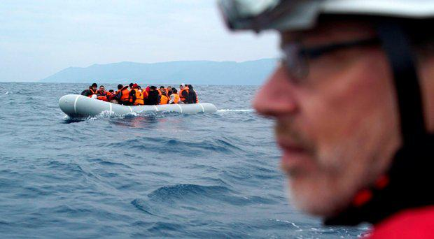 A German rescuer volunteer escorts with his vessel a dinghy with refugees and migrants as they arrive from the Turkish coast to the northeastern Greek island of Lesbos. File picture.