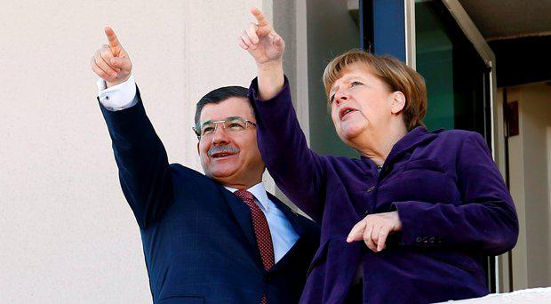 Turkish Prime Minister Ahmet Davutoglu and German Chancellor Angela Merkel gesture as they pose on balcony during their meeting in Ankara, Turkey February 8, 2016