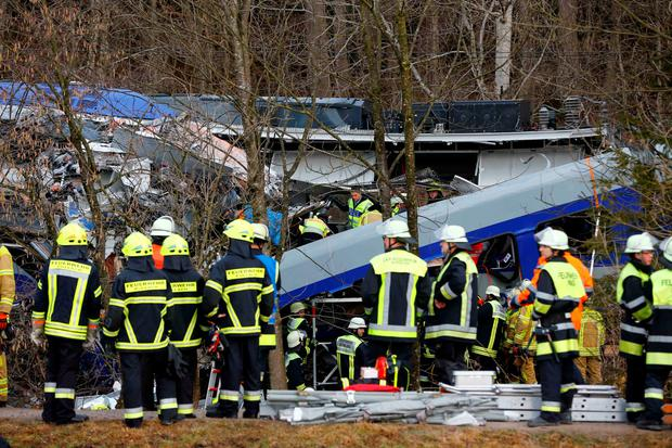 Rescue personnel stand in front of two trains that collided head-on near Bad Aibling, southern Germany, Tuesday, Feb. 9, 2016