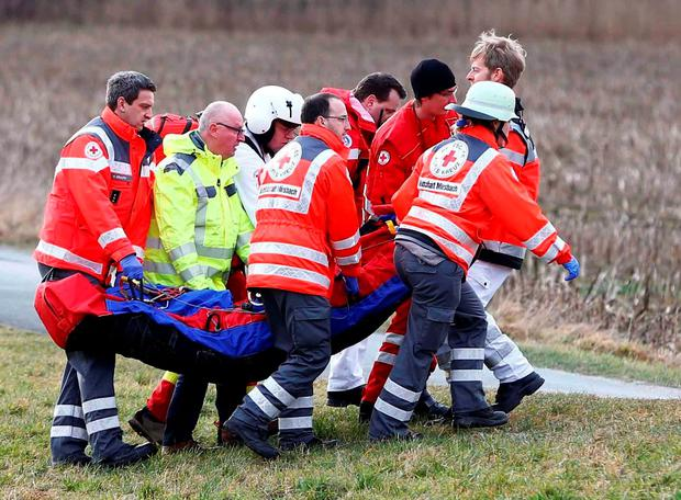 Rescue personnel carry an injured person near the site where two trains collided head-on near Bad Aibling, southern Germany, Tuesday, Feb. 9, 2016