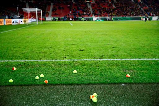 Tennis balls thrown onto pitch by fans during the match