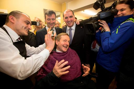 Taoiseach Enda Kenny gets a trim from barber Bega el-Feky watched by local FG candidate Paul Kehoe (second from right) in Enniscorthy, Co Wexford. Photo: Mark Condren