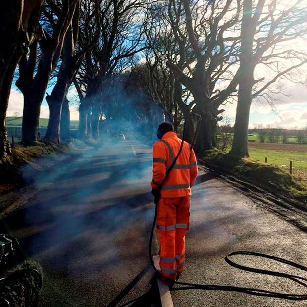 Undated handout photo taken with permission from the Twitter feed of Natasha Millar of red faced contractors who painted road markings on an iconic tree-lined avenue made famous by TV show Game Of Thrones as they returned to burn them off again Photo @natasha_utv/PA Wire