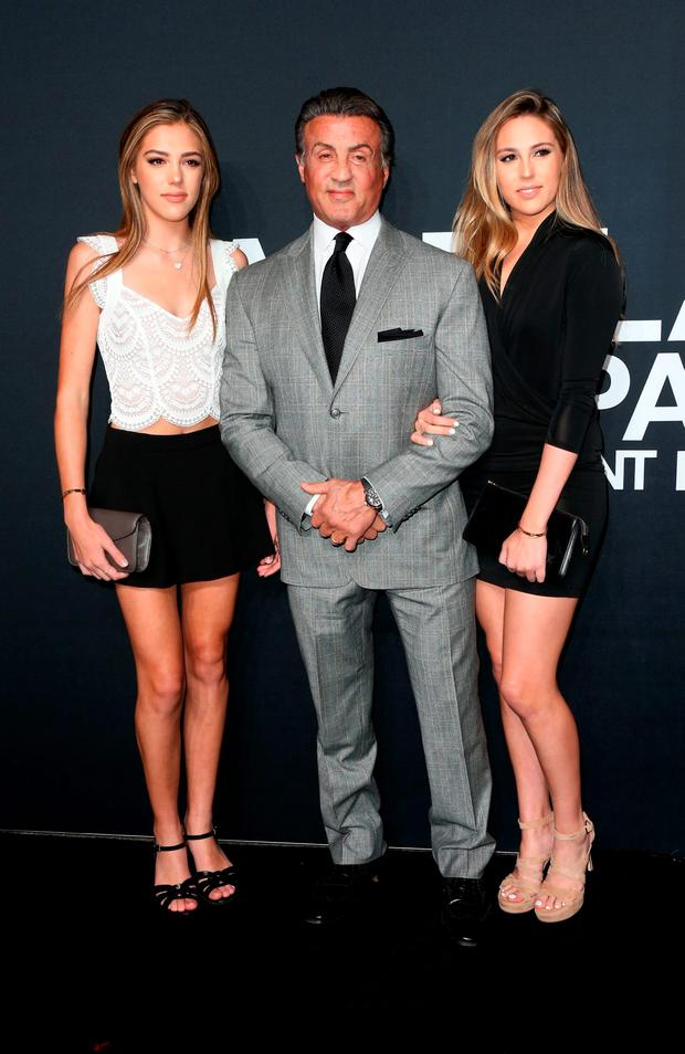 Actor Sylvester Stallone (center) and his daughters Sistine Stallone (L) and Sophia Stallone (R) attend the Saint Laurent show at The Hollywood Palladium in Los Angeles, California. (Photo by Frederick M. Brown/Getty Images)
