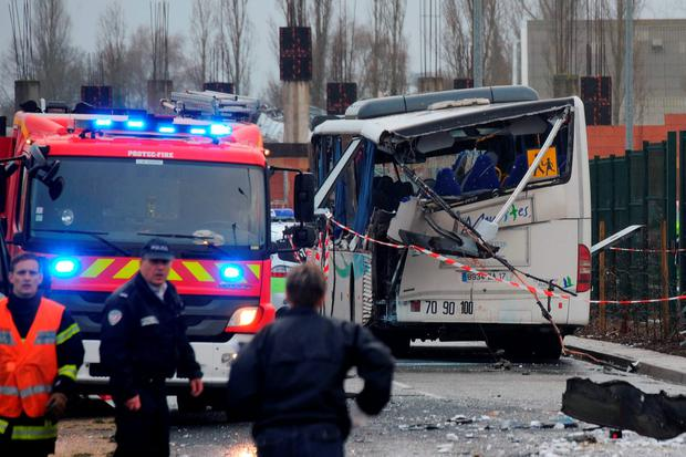 A French police officer stands near the wreckage of a school minibus after it crashed into a truck near Rochefort on February 11, 2016, killing at least six children, police said, a day after another road accident involving a school bus left two youngsters dead