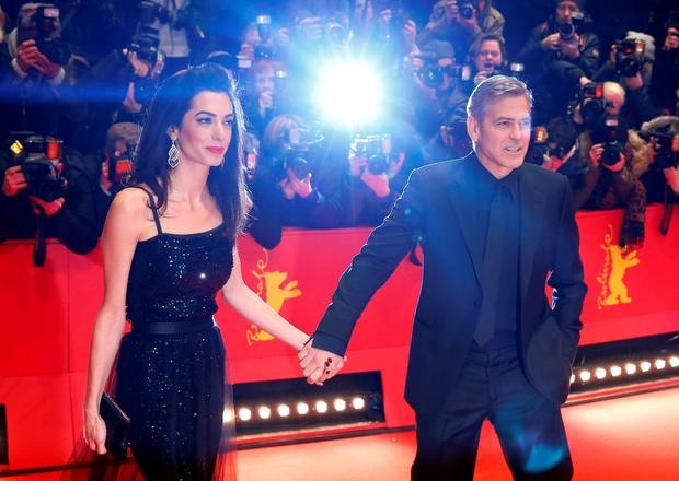US actor George Clooney, right, and his wife Amal Clooney arrive at the red carpet for