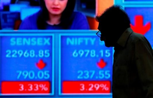 A man looks at a screen displaying news of markets update inside the Bombay Stock Exchange (BSE) building in Mumbai, India. Photo: Reuters