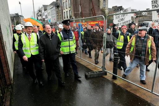 An Taoiseach Enda Kenny T.D. escorted by Gardai as he passes a small group of protesters at the turning of the sod on the €50m Cork Event Centre, Cork city. Photo: Daragh McSweeney/Provision