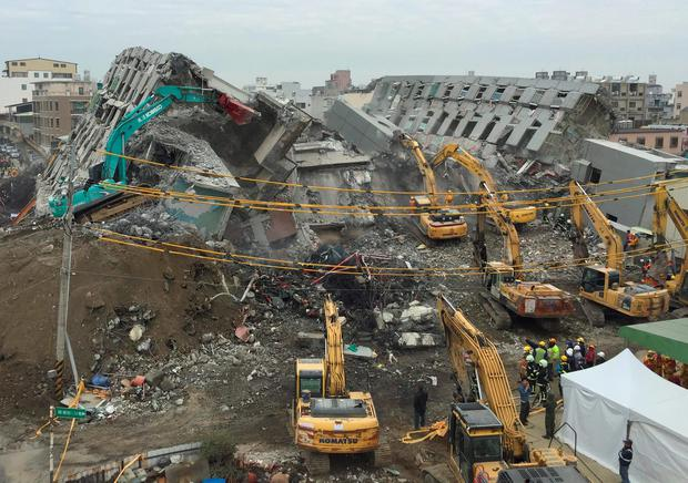 Rescue workers using excavators continue to search the rubble of a collapsed building complex in Tainan, Taiwan, Wednesday, Feb. 10, 2016. (AP Photo/Annie Ho)