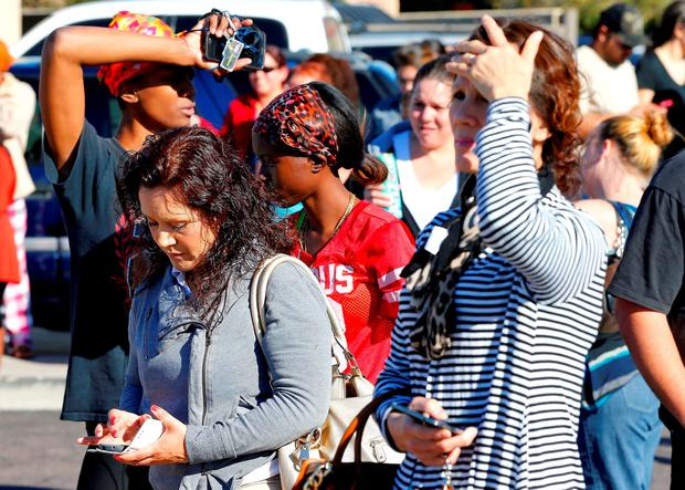 Parents wait to reunite with their children, Friday, Feb. 12, 2016, in Glendale, Ariz. after two teens were shot Friday at Independence High School in the Phoenix suburb. (AP Photo/Matt York)