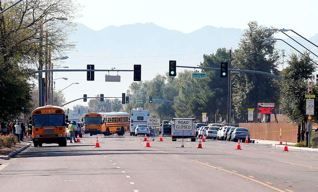Buses make their way to bring parents waiting to reunite with their children, Friday, Feb. 12, 2016, in Glendale, Ariz. after two teens were shot Friday at Independence High School in the Phoenix suburb. (AP Photo/Matt York)